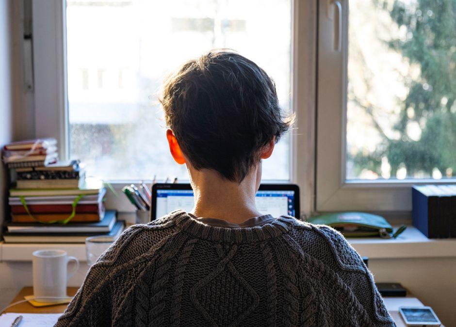 Kobieta siedząca tyłem przy komputerze