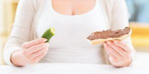 Kobieta w ciąży je kanapkę z Nutellą i ogórka