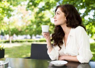Kobieta w ciąży pije kawę