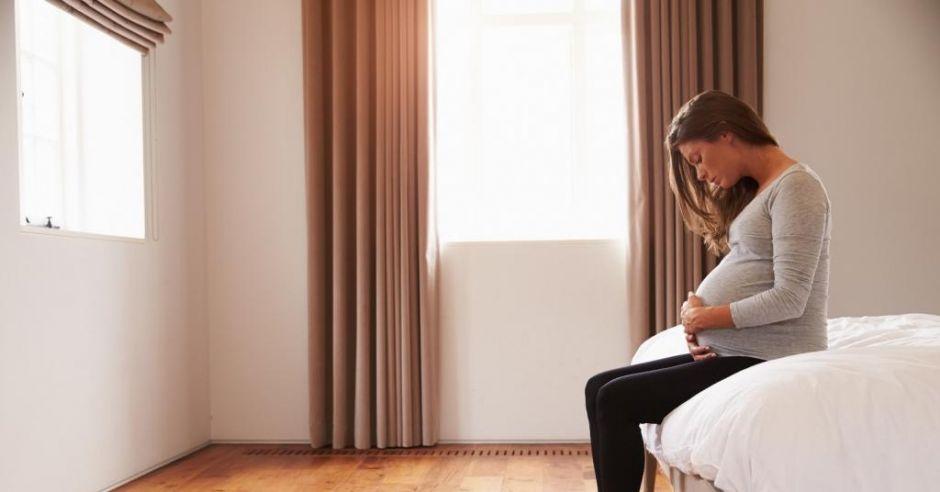 Kobieta w ciąży siedzi na brzegu łóżka