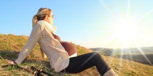 Kobieta w ciąży w górach z kijkami nordic walking