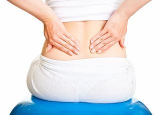 Kobieta w ciązy z bólem kręgosłupa trzyma się za plecy