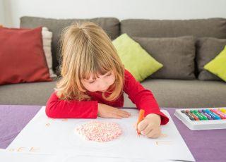 Leworęczna dziewczynka wykonuje pracę plastyczną