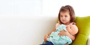 mała dziewczynka bawi się lalką dzidziusiem