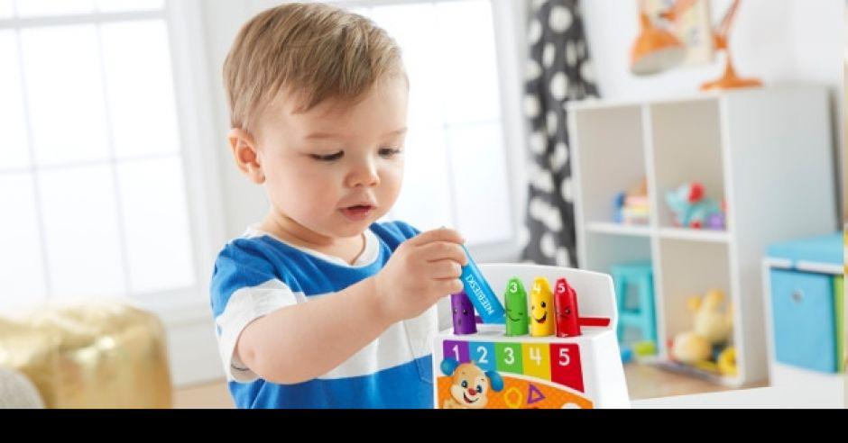 Małe dziecko bawi się zabawką Fisher Price