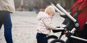 małe dziecko idzie trzymając się wózka