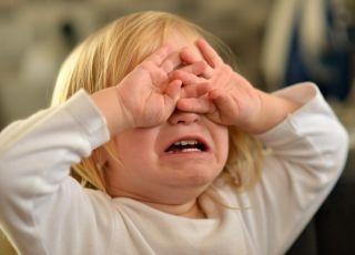 Małe dziecko płacze i zakrywa twarz rączkami