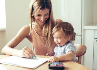 mama bawi się z córeczką przy stole - rysowanie