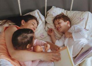 Mama czyta dzieciom w łóżku bajkę