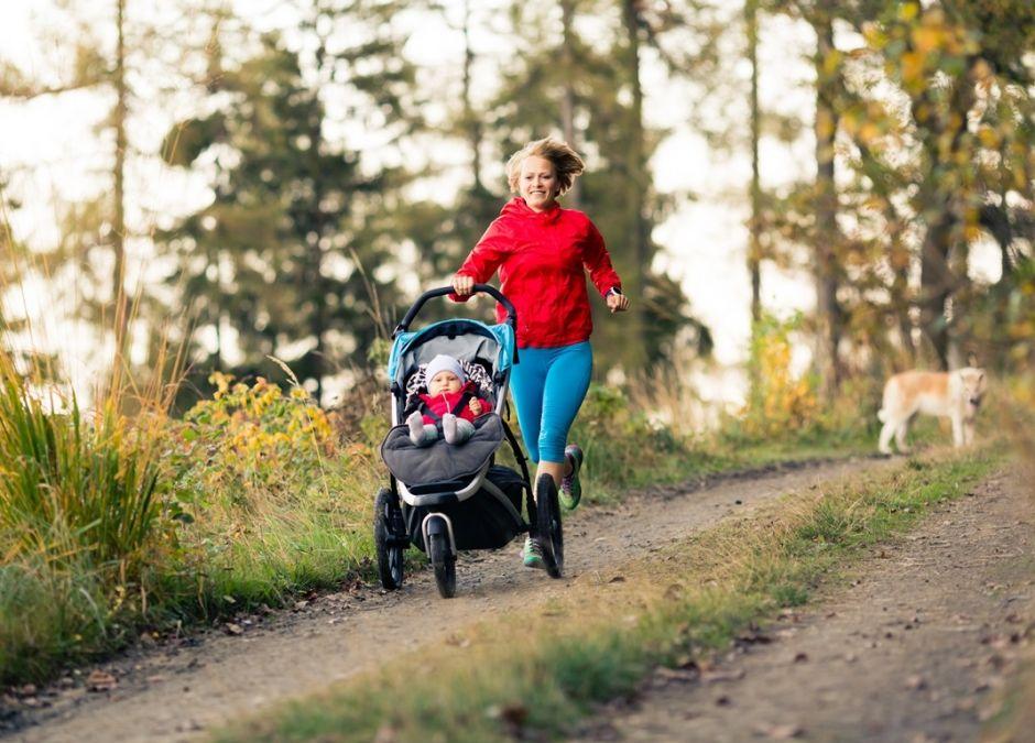 mama na spacerze w lesie biega z dzieckiem w wózku i psem