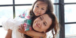 mama podnosi córkę, dziecko przytula się do mamy
