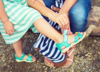 mama poprawia bucik letni dziecku
