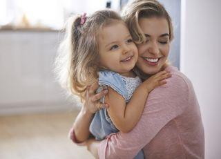 Mama przytula córeczkę i uśmiecha się