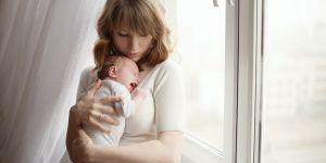 Mama przytula dziecko płaczące (ma kolkę)