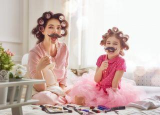 Mama siedzi na łóżku z córką i bawią się sztucznymi wąsami