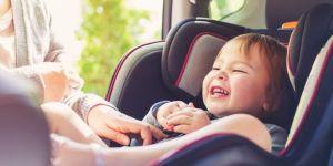 Mama zapina córeczkę w bezpiecznym foteliku samochodowym