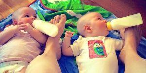 Matka karmi bliźnięta przytrzymując butelki stopami