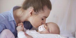 Młoda mama całuje niemowlę w policzek