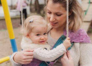 Młoda mama z dzieckiem na placu zabaw