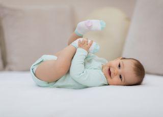 niemowlę leży i się śmieje, bawi się nóżkami