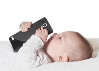 Niemowlę leży z telefonem w ręce