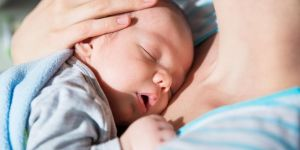 Niemowlę śpi u mamy na rękach