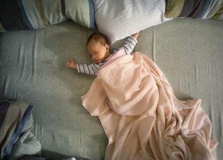 Niemowlę śpi w dużym łóżku