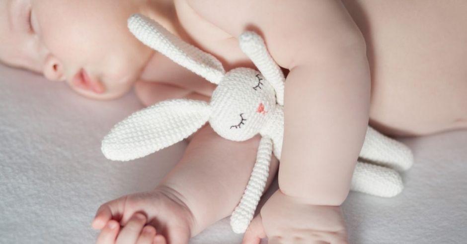 Niemowlę śpi w łóżeczku, przytulając pluszowego króliczka