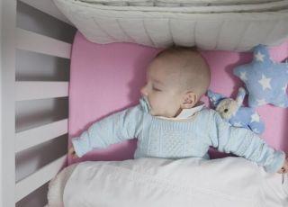 Niemowlę śpi w łóżeczku ze smoczkiem