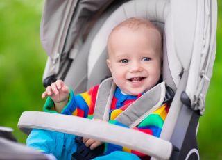 niemowlę uśmiecha się na spacerku w wózku