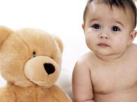 niemowlę z misiem, nauka siadania, rozwój dziecka, rozwój niemowlaka