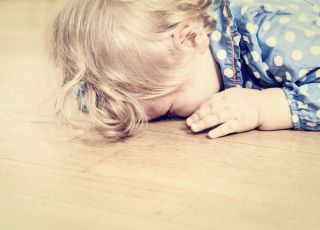 Obrażone dziecko leży na podłodze
