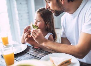 ojciec karmi córeczkę zdrowym jedzeniem
