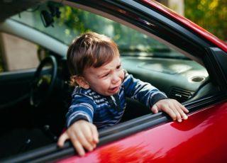 Płaczący chłopiec próbuje wyjść z samochodu przez okno