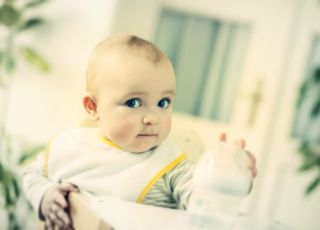 Przekarmiane niemowlę sięga po butelkę z mlekiem
