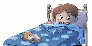 Przestraszony chłopiec leży w łóżku i boi się zasnąć