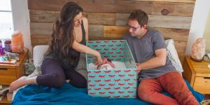 Rodzice leżą w łóżku z niemowlęciem w pudełku