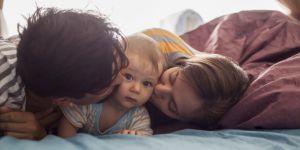 Rodzice z dzieckiem leżą w łóżku