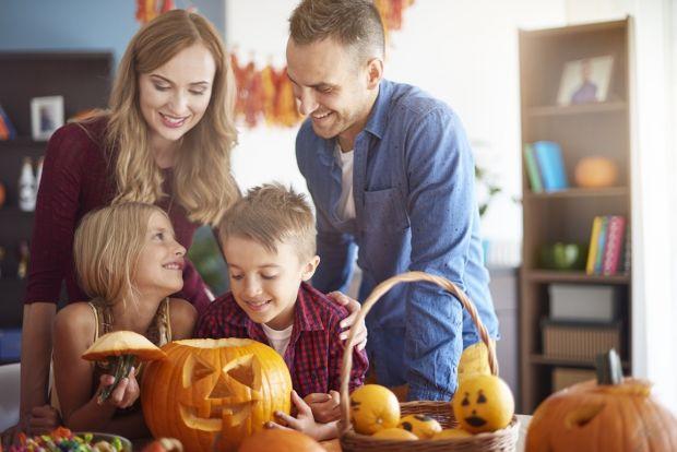 rodzice z dziećmi wspólnie wycinają wzory na dyni w halloween