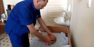 Rosyjski lekarz ortopeda bada noworodka