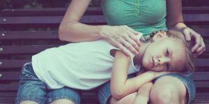 Smutna dziewczynka leży na kolanach mamy siedzącej na ławce