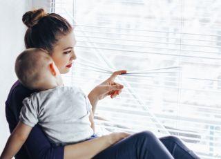 smutna mama siedzi z dzieckiem przy oknie