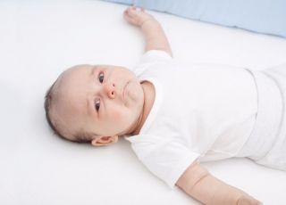 Smutne niemowlę zostawione przed snem przez mamę w łóżeczku