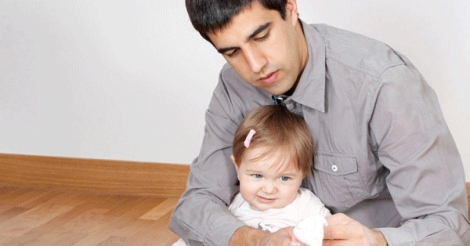 Tata próbuje ubrać dziecko