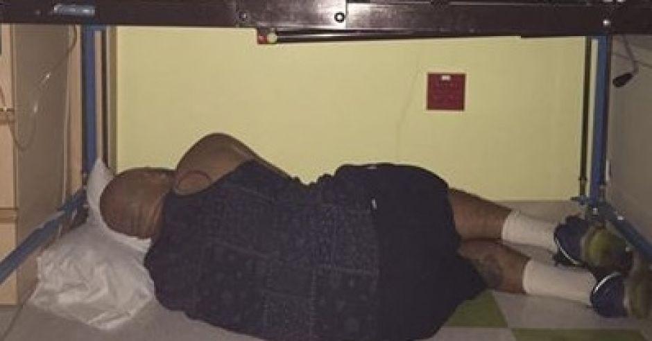 Tata śpi pod łóżeczkiem nowo narodzonego dziecka