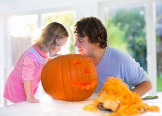 Tata z córką wycinanją dynię na Halloween, by zrobić lampion z dyni.