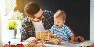 tata z dzieckiem bawią się drewnianym samochodzikiem