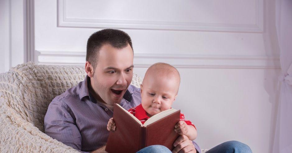Tata z niemowlakiem czytającym książkę