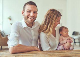 Uśmiechnięci rodzice siedzą przy stole z niemowlakiem