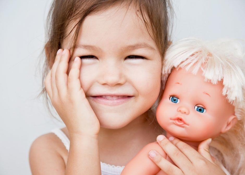 uśmiechnięta dziewczynka z lalką